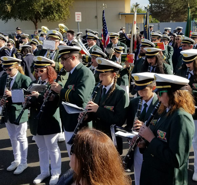 Many uniformed musicians of different ages in alignment and playing music together