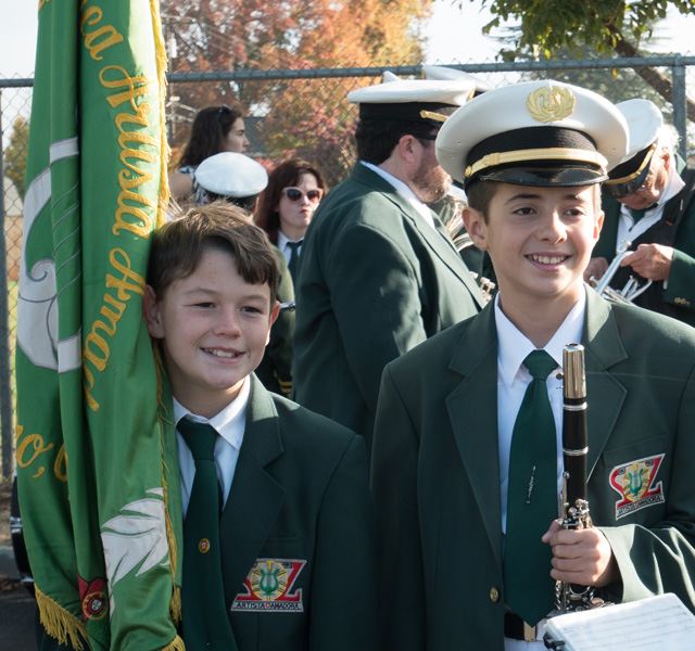 Two young members posed and smiling, holding a clarinet and a flag
